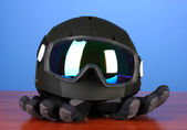 Winter sport glasses, helmet and gloves, on blue background — Stock Photo