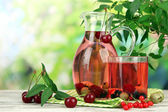 Pitcher and glass of compote with summer berries on natural background — Stock Photo