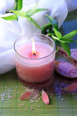 Beautiful candle on bamboo mat — Stock Photo