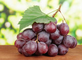 Ripe delicious grapes on table on bright background — Stock Photo