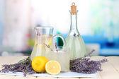 Lavender lemonade in glass bottle and jug, on napkin, on bright background — Stock Photo