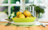 Boiled potatoes on platens on on napkins on wooden table on window background — Stock Photo