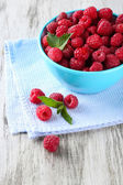 Ripe sweet raspberries in bowl on wooden background — Stock Photo