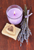 Lavender candle with fresh lavender, soap on wooden background — Stock Photo