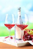 Kieliszków wina w serwetkę na tacę na drewnianym stole na tle przyrody — Zdjęcie stockowe
