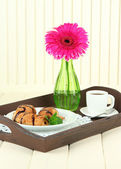 Wooden tray with breakfast, on wooden table, on light wooden background — Stock Photo