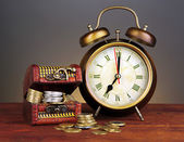 Antique clock and coins on wooden table on black background — Stock Photo