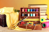 Sewing kit in wooden box with books and cloth table on bright background — Stock Photo
