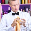 Stock Photo: Bartender wipes glasses at work