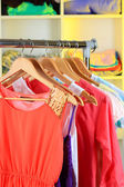 Variety of clothes on wooden hangers on shelves background — Stock Photo