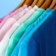 Variety of casual shirts on wooden hangers,on blue background — Stock Photo #29423253