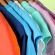 Variety of casual shirts on wooden hangers,on blue background — Stock Photo