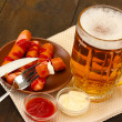 Beer and grilled sausages on wooden background — Stock Photo #29423869
