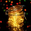 Stock Photo: Christmas lights in glass bottle on blur lights background