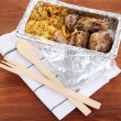 Stock Photo: Food in box of foil on napkin on wooden background
