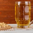 Beer in glass crunches, and nuts on napkin on table on wooden background — Stock Photo