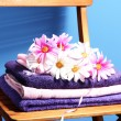 Stock Photo: Towels and flowers on wooden chair on blue background