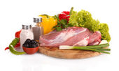 Raw meat and vegetables on a wooden board isolated on white — Stock Photo