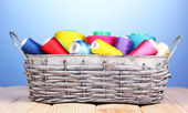 Bright threads in basket on wooden table on blue background — Stock Photo