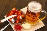 啤酒和烤的香肠木制背景上 — 图库照片