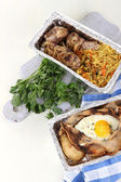 Food in boxes of foil on napkin on wooden board isolated in white — Stock Photo
