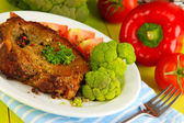 Piece of fried meat on plate on wooden table close-up — Stock Photo