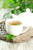 Teapot and cup of herbal tea with fresh mint on wooden table — Stock Photo