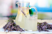 Lavender lemonade in glass jug, on napkin, on bright background — Stock Photo