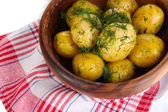Boiled potatoes on wooden bowl on napkins — Stock Photo