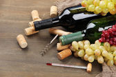 Bottles of wine, grapes and corks on wooden background — Stock Photo