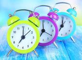 Tablo üzerinde mavi arka plan üzerinde renkli çalar saatler — Stok fotoğraf