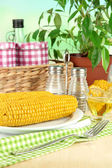 Flavored boiled corn on plate on wooden table on natural background — Stock Photo