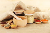 Assortment of spices in wooden spoons and jars, on wooden background — Stock Photo