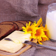 Butter on wooden holder surrounded by bread and milk on sacking background — Stock Photo