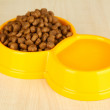 Dry dog food in bowl on wooden background — Stock Photo
