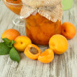 Apricot jam in glass jar and fresh apricots, on wooden background — Stock Photo