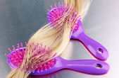 Blond curls brushing two combs on metalic background — Stock Photo