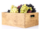 Assortment of ripe sweet grapes in wooden crate, isolated on whit — Stock Photo