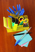 Office equipment in yellow stationary holder on wooden table — Stock Photo