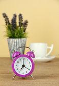 фиолетовый будильник на стол на бежевом фоне — Стоковое фото