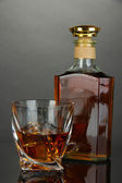 Glass of whiskey with bottle, on dark background — ストック写真
