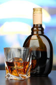 Glass of liquor with bottle, on dark background — Стоковое фото