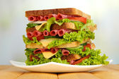 Huge sandwich on wooden table, on light background — Foto Stock