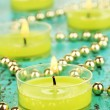 Stock Photo: Lighted candles with beads on green background