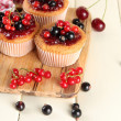 Tasty muffins with berries on white wooden table — Stock Photo #29520947
