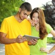 Two happy young students with laptop in park — Stock Photo #29521117