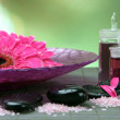 Gerbera flowers on water and spa stones on bamboo mat — Stock Photo