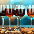 Stock Photo: Glasses of liquors with almonds and coffee grains, on bright background