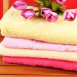 Stock Photo: Towels and flowers on wooden chair on red background