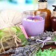 Stock Photo: Still life with lavender candle, soap, massage balls, bottles, soap and fresh lavender, on wooden table on bright background